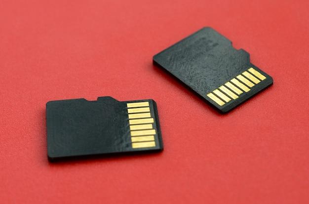Zwei kleine micro-sd-speicherkarten liegen auf rotem grund. ein kleiner und kompakter daten- und informationsspeicher
