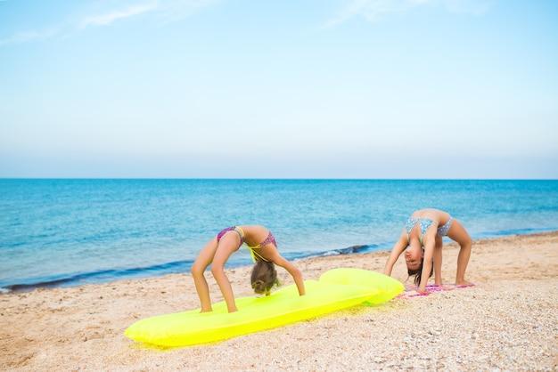 Zwei kleine positive turnerinnenschwestern machen übungen, während sie sich an einem sandstrand entspannen