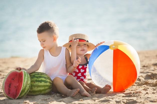Zwei kleine schöne kinder am strand mit wassermelonen. nette kinder, die nahe am meer lächelnd spielen. fröhliche kinder.