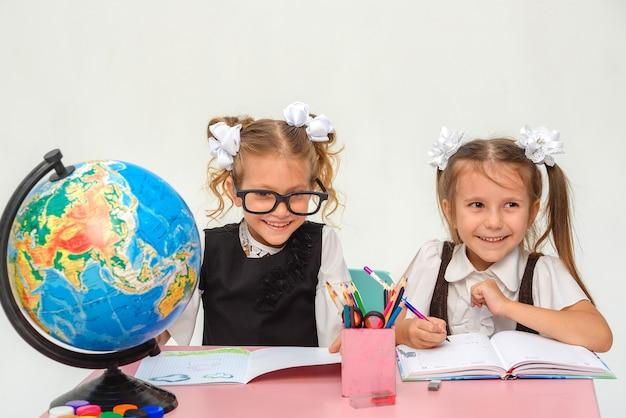 Zwei kleine schulmädchen denken im klassenzimmer isolieren