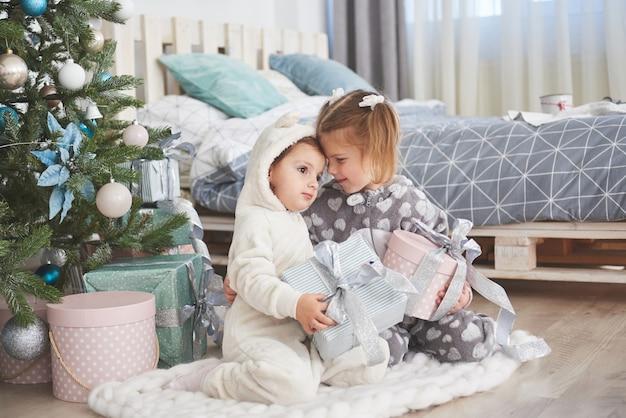 Zwei kleine schwestermädchen öffnen morgens ihre geschenke am weihnachtsbaum auf dem deck