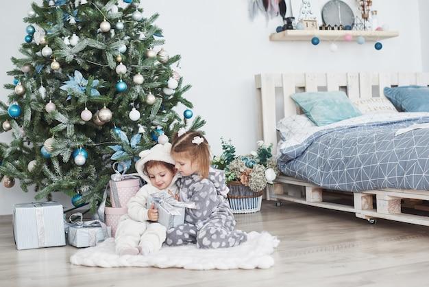 Zwei kleine schwestermädchen öffnen morgens ihre geschenke am weihnachtsbaum