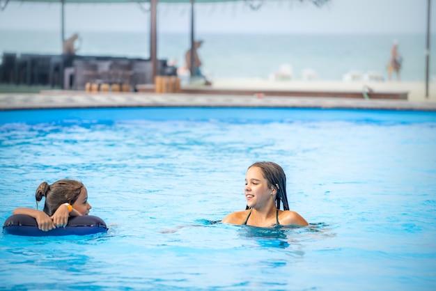 Zwei kleine schwestermädchen schwimmen in einem großen pool mit klarem blauem wasser in der nähe des hotels