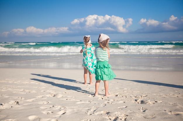 Zwei kleine schwestern, die am tropischen strand in mexiko am sonnigen tag laufen