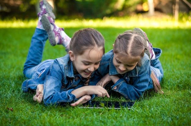 Zwei kleine schwestern, die auf grünem gras liegen und auf tablet spielen