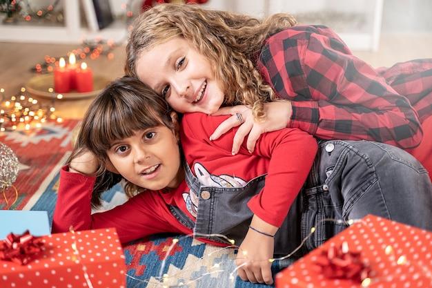 Zwei kleine schwestern, die mit geschenkbox in weihnachtsatmosphäre spielen