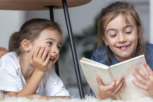 Zwei kleine schwestern haben spaß beim gemeinsamen lesen eines buches, während sie in ihrem zimmer auf dem boden liegen.