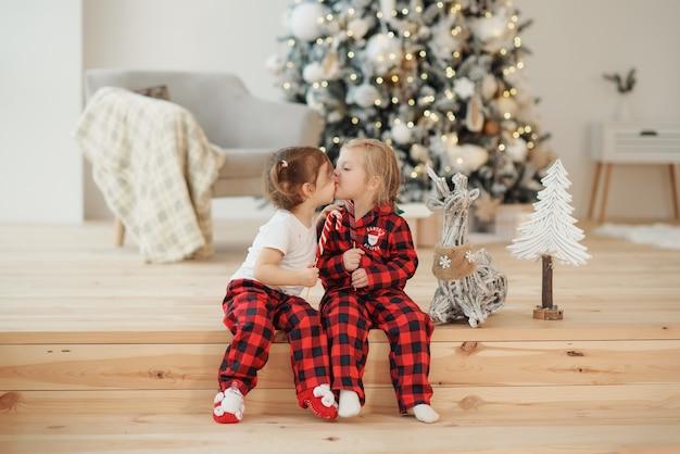 Zwei kleine schwestern im roten pyjama sitzen am weihnachtsmorgen im wohnzimmer und essen süßigkeiten. familienfeier, umarmungen und küsse