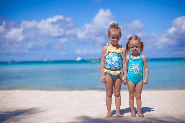 Zwei kleine schwestern in schönen badeanzügen am tropischen strand in philippinen