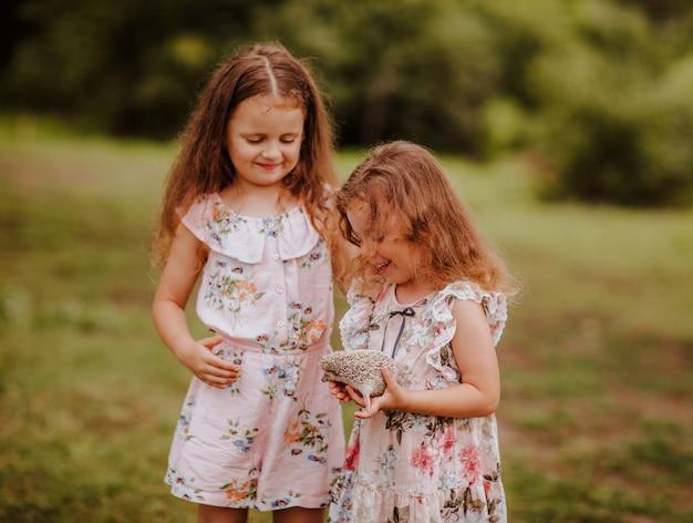 Zwei kleine schwestern mit einem igel