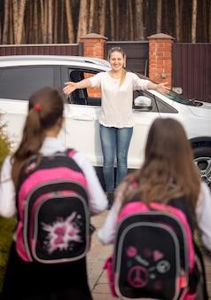 Zwei kleine schwestern mit rucksäcken laufen zur mutter und treffen sie nach dem unterricht in der schule Premium Fotos