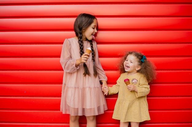 Zwei kleine schwestern stehen am roten zaun und essen eis. ein brünettes mädchen mit zöpfen und das zweite lockige baby
