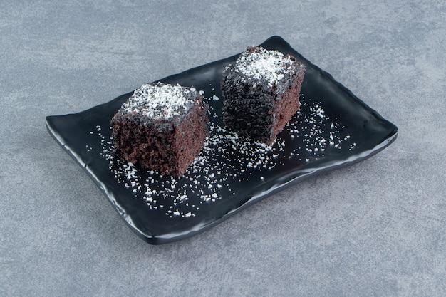 Zwei kleine stücke brownie auf einem dunklen teller