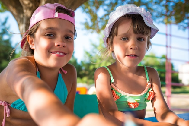 Zwei kleine süße mädchen, die draußen puppen spielen, während sie an einem heißen sommertag am strand entspannen