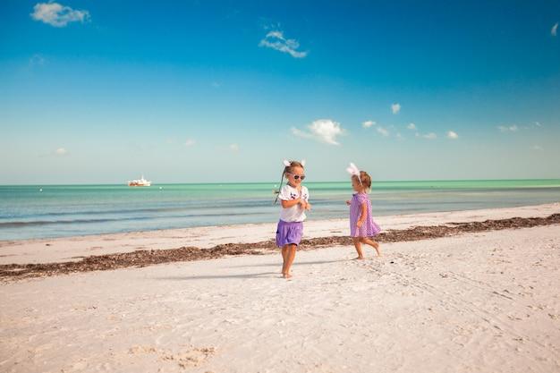 Zwei kleine süße mädchen in osterohren haben spaß am exotischen strand