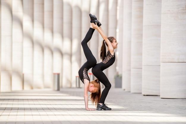 Zwei kleine tänzerinnen ballerinas in schwarzen enganliegenden kostümen tanzen vor der kulisse des stadtbildes.