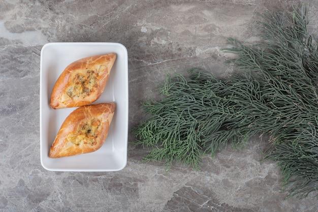 Zwei kleine türkische pides auf einer platte neben tannenzweigen auf marmoroberfläche