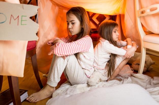 Zwei kleine verärgerte schwestern, die rücken an rücken im schlafzimmer auf dem boden sitzen