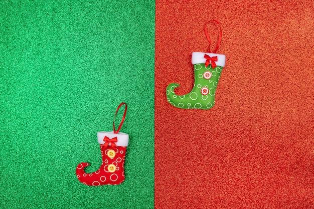 Zwei kleine weihnachtssymbole grüner und roter strumpf gelegen auf einem rot-grünen glänzenden. santa jahr der ratte. . urlaub. geschenk-bestellungen. neujahrs zubehör.