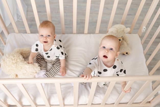 Zwei kleine zwillinge, bruder und schwester, sitzen 8 monate im schlafanzug in der krippe und schauen in die kamera