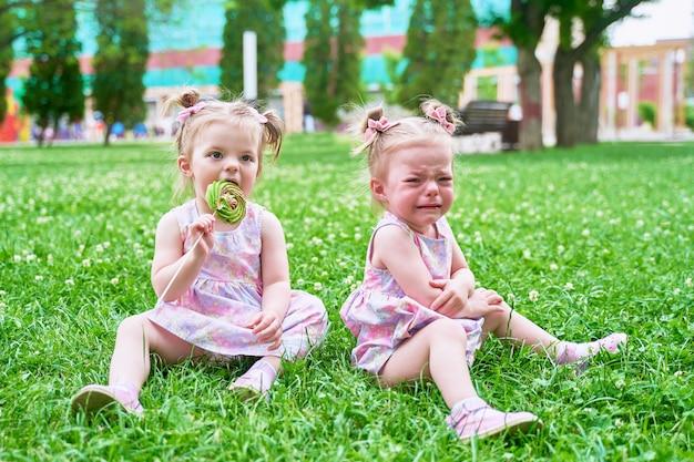 Zwei kleine zwillingsmädchen teilten die süßigkeiten nicht