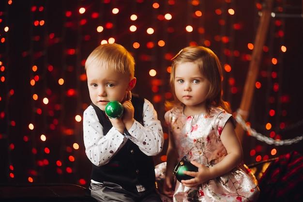 Zwei kleinkinder, die mit grünen weihnachtsbögen spielen, nähern sich dekoration und weihnachtsbaum