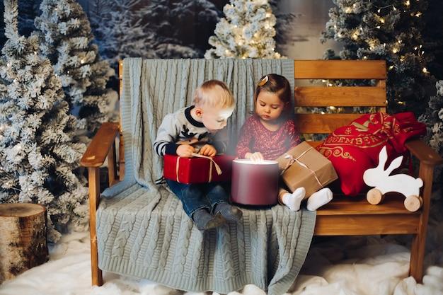 Zwei kleinkinder, die mit weihnachten nahe dekoration und weihnachtsbaum spielen
