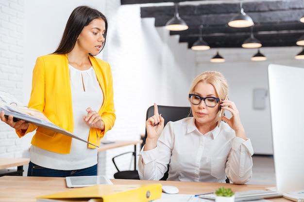 Zwei kluge geschäftsfrauen diskutieren ideen am tisch im büro