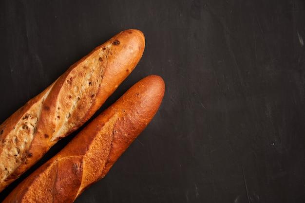 Zwei knusprige französische baguettes liegen dunkelschwarze sesamkörner mit tischhintergrund