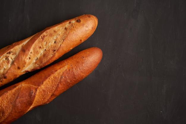 Zwei knusprige französische baguettes liegen dunkelschwarzer tischhintergrund