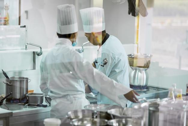 Zwei köche, die in weißen kochuniformen kochen in der küche kochen, um den kunden im hotelrestaurant essen zu servieren
