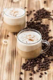 Zwei köstliche cappuccinos mit schokoladenstückchen auf einem holztisch mit kaffeebohnen.