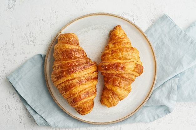 Zwei köstliche hörnchen auf platte und heißem getränk im becher. französisches frühstück am morgen mit frischem gebäck