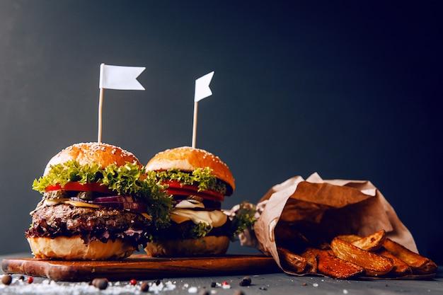 Zwei köstliche, köstliche hausgemachte burger zum hacken von rindfleisch. auf dem holztisch.