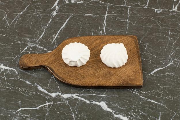 Zwei köstliche marshmallows auf holzschneidebrett.