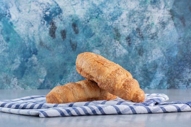 Zwei köstliche süße croissants mit tischdecke auf steinhintergrund.
