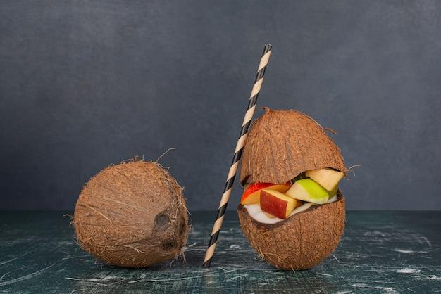 Zwei kokosnüsse mit stroh und apfelscheiben