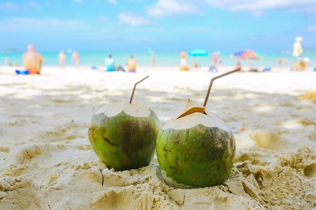 Zwei kokosnüsse mit strohhalmen liegen am strand im hintergrund des strandes mit menschen. vorderansicht