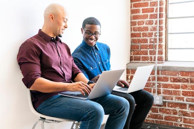 Zwei kollegen arbeiten gemeinsam an ihren laptops