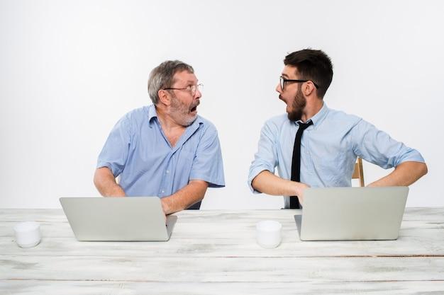 Zwei kollegen arbeiten im büro auf weiß zusammen