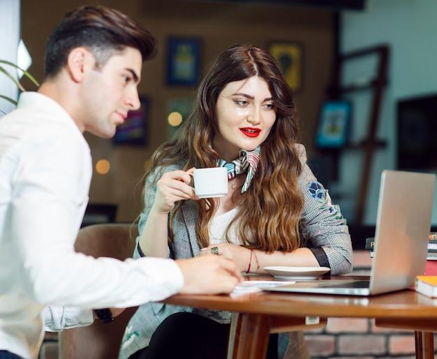 Zwei kollegen, die coffea haben und ein projekt in der sitzzone eines büros überprüfen.