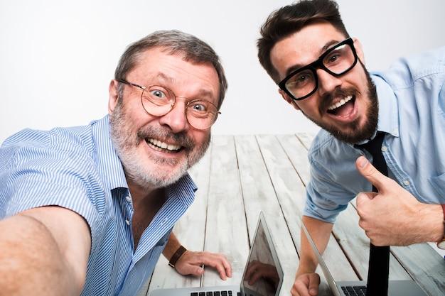 Zwei kollegen, die das bild zu sich nehmen, sitzen selbst im büro