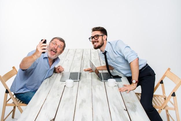 Zwei kollegen, die ihnen das foto machen, sitzen selbst im büro