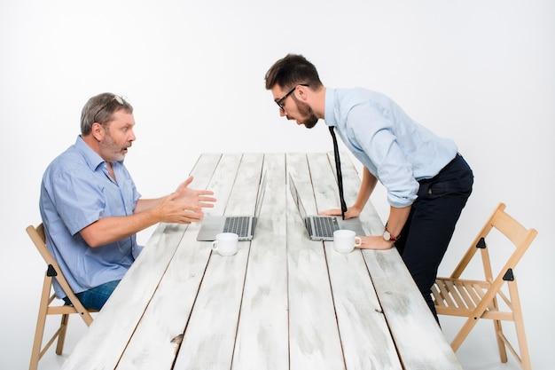 Zwei kollegen, die im büro auf grau zusammenarbeiten