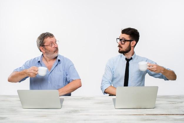 Zwei kollegen, die im büro auf weiß zusammenarbeiten