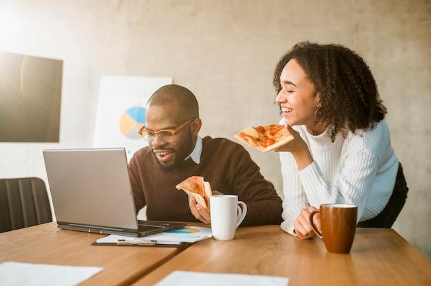 Zwei kollegen, die während einer bürobesprechungspause pizza essen