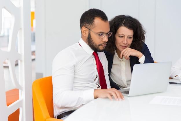 Zwei kollegen, die zusammen laptopschirm betrachten