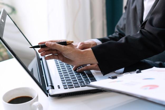 Zwei kollegen diskutieren daten mit computer-laptop auf schreibtisch tisch im büro. schließen sie die analyse und das strategiekonzept des geschäftsteams.