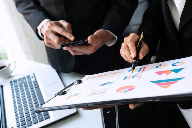 Zwei kollegen diskutieren daten mit smartphone auf schreibtisch tisch. schließen sie die analyse und das strategiekonzept des geschäftsteams.