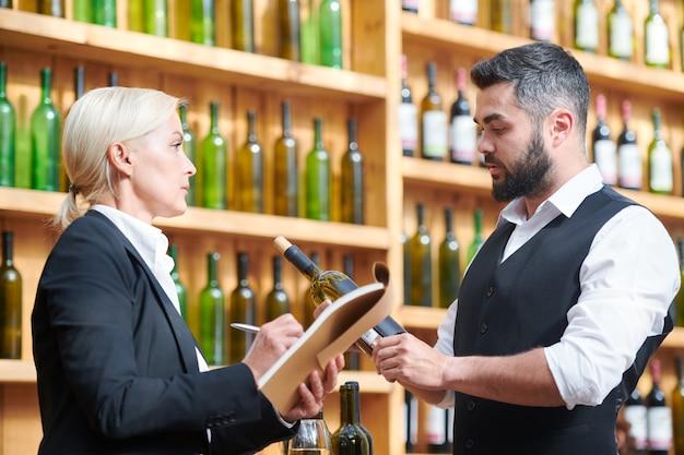 Zwei kollegen diskutieren neue art von wein, während junger mann flasche und blonde frau hält notizen im notizblock